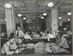 News room of the New York Times newspaper Right foreground, city editor. Two assistants, left foreground. City copy desk in middle ground, with foreign desk, to right; telegraph desk to left. Make-up desk in center back with spiral staircase leading to composing room. Copy readers go up there to check proofs. (Photo by Marjory Collins) http://www.loc.gov/pictures/item/2012647143/